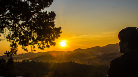 faintly visible: gold sunrise on the mountain and silhoutte human and pine tree landscape Stock Photo