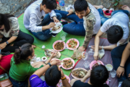 thai culture: blur shot Thai eating on mat and ground with old tradition Stock Photo