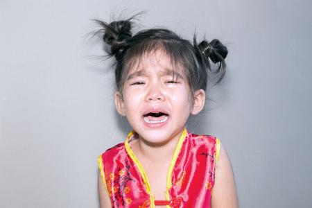 niña llorando en la suite chino sobre fondo claro