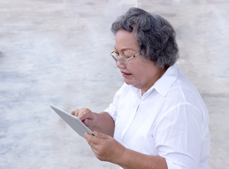 ibook: old asian grandmother watch and touch tablet on white background