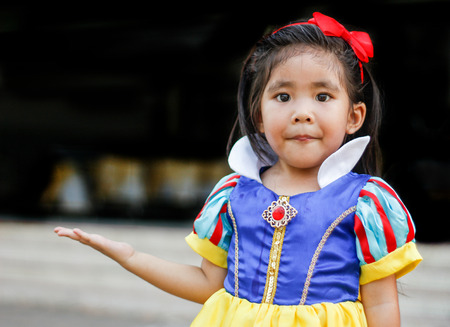 snowwhite: potrait princess dress with cute asian girl show hand for hold something Stock Photo