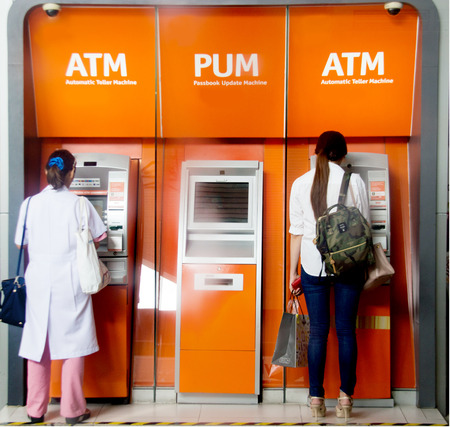 two woman use atm matchine for have a money in deference reason