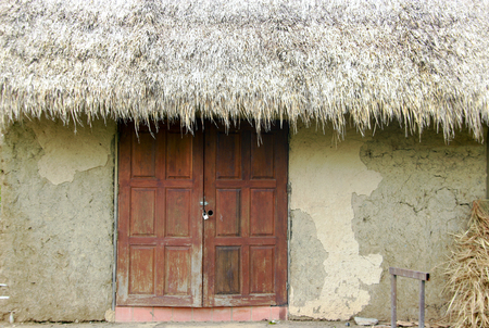 pannel: close up one pannel of old soil house building and straw roof of rural life Thailand