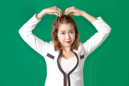 asian thai lady acting arm on head like heart symbol in businees wearing on green screen