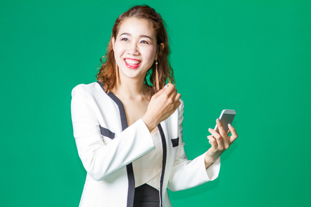 new generation: asian thai girl happy smile and look up with mobile phone in new generation concept
