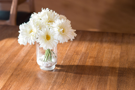 close up white artificial daisy flower in wase on wood table for background