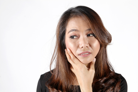 asian thai woman worry about shape of jaw face from hand acting Standard-Bild