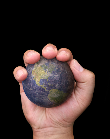world ball: abstract concept hand hold old iron world ball in one hand on black isolated background