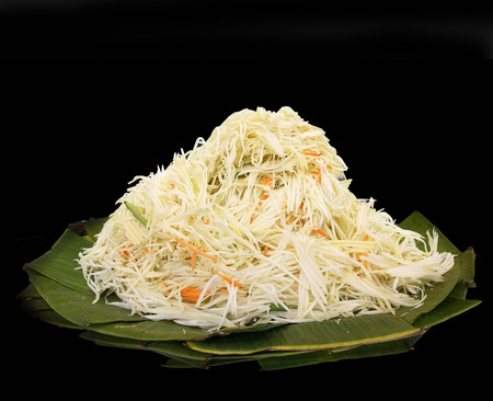 papaya slide ingredient for somtum favorite menu in thailand on banana leaf, black isolate background Stock Photo
