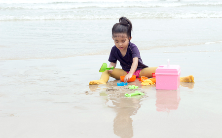 exersice: asian girl play sand beach having fun with plastic toy Stock Photo