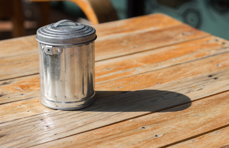 aluminum bin on wood table in sunny day for background
