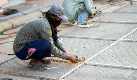safty: asian man cutting steel net cage with electrict saw with no safty  Stock Photo