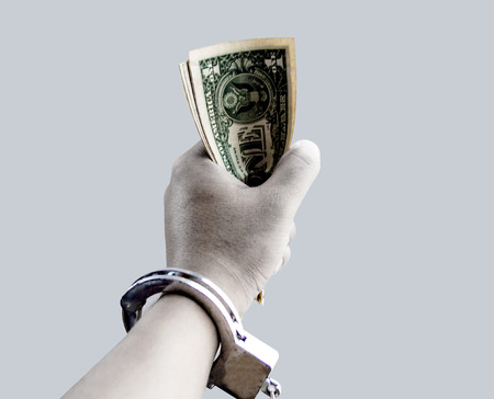 close up hand hold banknote with silver chain in corruption concept