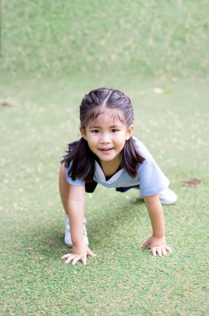 runing: asian girl put her finger to shues to start runing on green grass Stock Photo