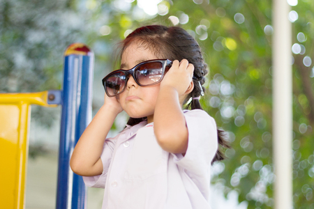 asian thai girl funny action with sunglasses on play park