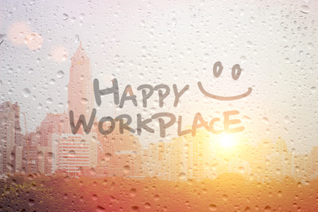place of work: draw smile symbol and happy workplace word in morning on window and town landscape