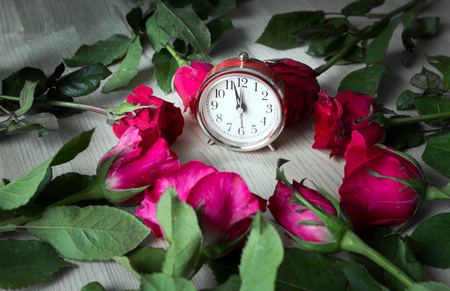 red and pink rose flower on wood table around clock in time concept