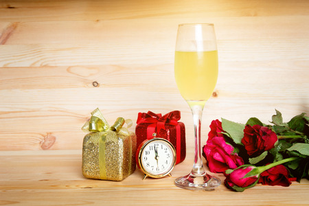 cerebrate: time to dating in valentine with champagne present rose flower on wood background
