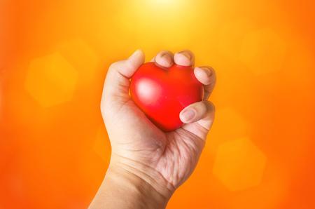 close up hand hold heart symbol on orange background Stock Photo