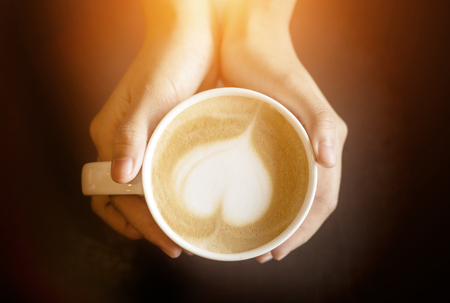latte art like heart shape in coffee cup with hand hold mug for warm in dark background