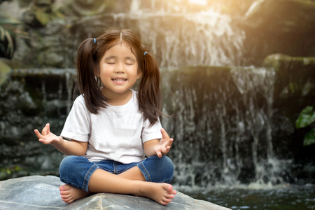 asian girl make meditaion in water fall nature Stock Photo
