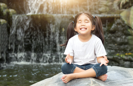 asian girl make meditaion in water fall nature with flare light Stock Photo