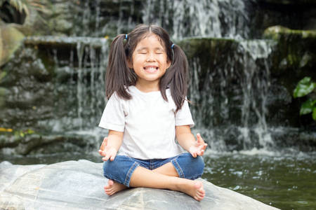 asian girl make meditaion in water fall nature forest to practice emotion control qulification