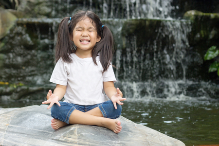 asian girl make meditaion in water fall nature forest to happy emotion control