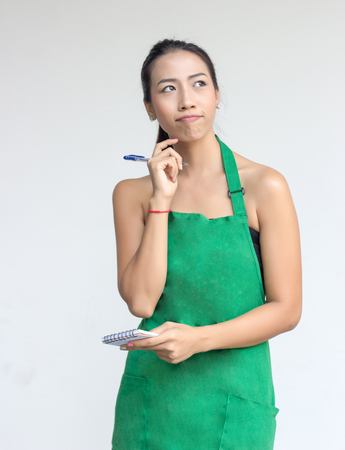 businesswoman with green apron think to list order with note and pen