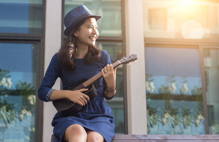 asian girl having fun play ukulele in bossanova song in summer time for take a rest in flare ligh