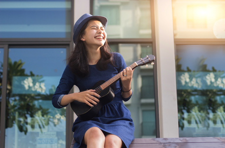 asian girl having fun play ukulele in bossanova song in summer time for take a rest