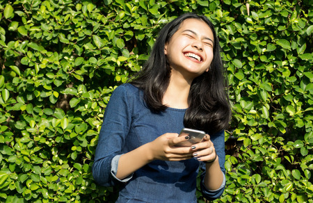 asian girl cute smile face in joke with mobile phone