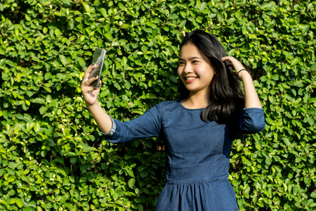 asian teenage selfy with smart phone with nice smile on green park background Stock Photo