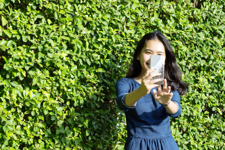 select focus face of asian girl take photo selfy on green background Stock Photo