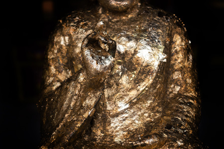 close up hand of sculpture Buddism with gold paper for praying tradition culture