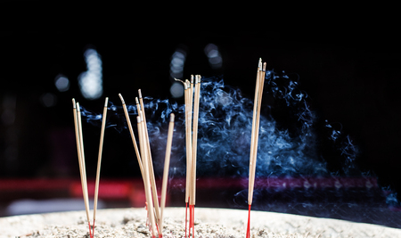 close up burning incense stick on sand box at temple in thailand with dark background toxic polution Stock Photo