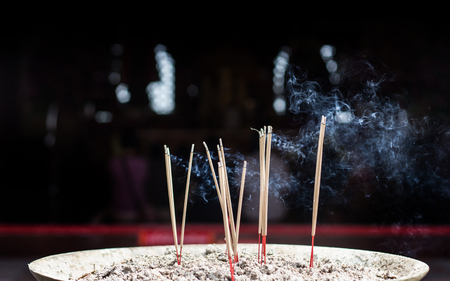 close up burning incense stick on sand box at temple in thailand with dark background and polution toxic in tradition