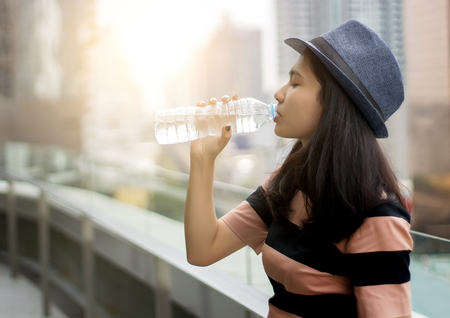 Aziatisch meisje drinkwater uit fles in ochtend licht op stedelijke stad achtergrond