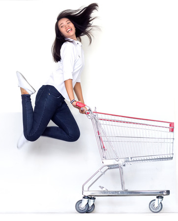 asian teen girl jump with shopping cart in shopaholic concept