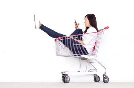 asian teen girl in shopping cart in shopaholic with mobile phone concept