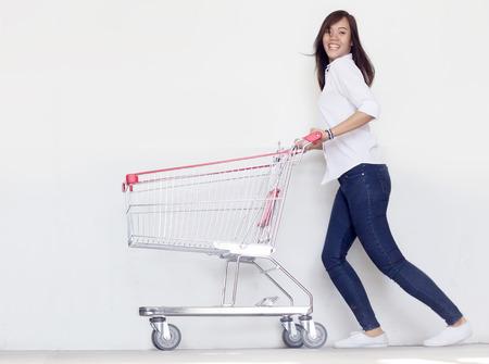 Aziatische fashionist tiener meisje hebben grappige actie met winkelwagen in liefde shopaholic concept