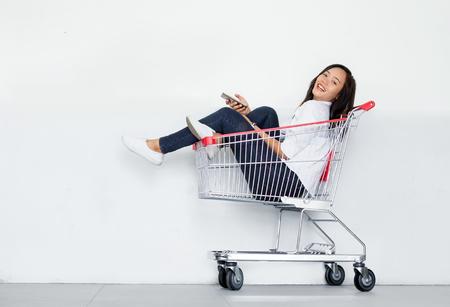 Aziatisch meisje gebruik mobiele telefoon in de winkelwagen toon winkelen online concept Stockfoto