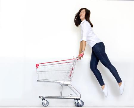 spostamento colpo ragazza adolescente asiatico ijump con carrello della spesa nel concetto di shopaholic