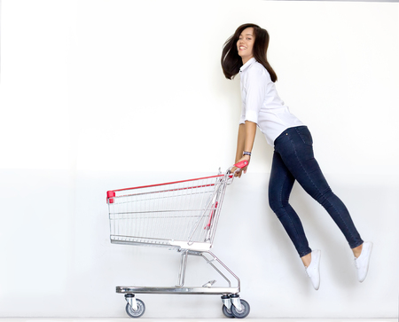 moving shot asian teen girl ijump with shopping cart in shopaholic concept