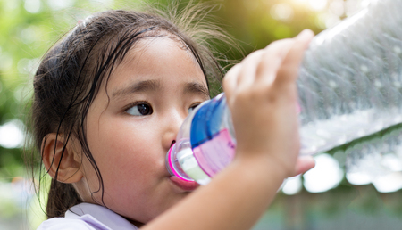 asian girl bottom up drink water with plastic bottle in park hot day