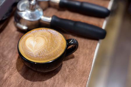hot temper: close up top of latte art in black ceramic cup on coffee matchine