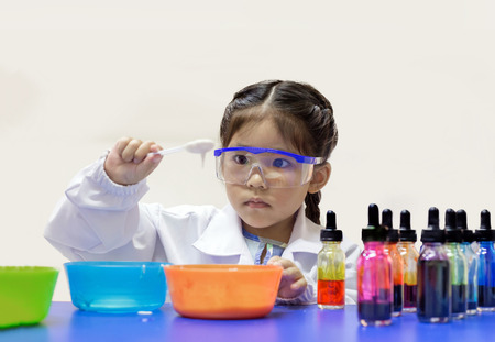 cute asian kid in scientist uniform and learn chemical lab