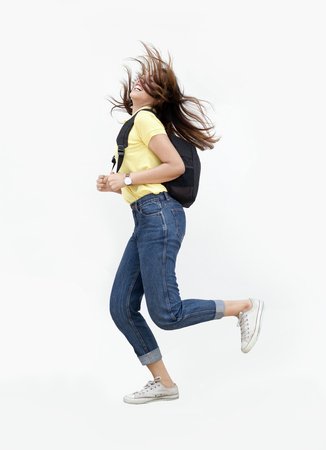 portrait happy teenage asian girl jump action with backpack and casual wearing to university or classroom concept on white isolate background Stock Photo