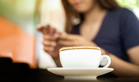 close up stroopwaffle on hot coffee cup and blur woman waiting eat and chat with mobile on vocation day Stock Photo