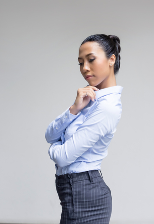 super woman: confidence action portrait model asian lady in business look with blue shirt on gray background